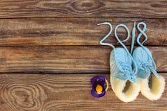 2018 nouvelles années écrites des dentelles des chaussures et de la tétine du ` s d'enfants sur le vieux fond en bois Images libres de droits