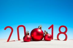 Nouvelles années de fête de concept avec des boules de Noël une plage tropicale ensoleillée avec 2018 en rouge et l'espace de cop Photos stock
