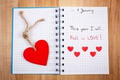 Nouvelles années de résolutions écrites au carnet, aux coeurs en bois et de papier rouges Images libres de droits