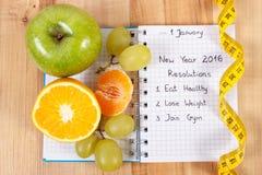 Nouvelles années de résolutions écrites dans le carnet et le ruban métrique Photo stock