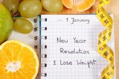 Nouvelles années de résolutions écrites dans le carnet et le ruban métrique Photographie stock