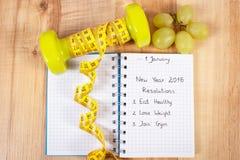 Nouvelles années de résolutions écrites dans le carnet et les haltères de centimètre Image stock