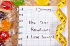 Nouvelles années de résolutions écrites dans le carnet, les sucreries et le ruban métrique Images libres de droits