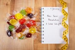 Nouvelles années de résolutions écrites dans le carnet, les sucreries et le ruban métrique Image stock