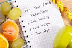 Nouvelles années de résolutions écrites en carnet et fruits, haltères de centimètre Photos stock