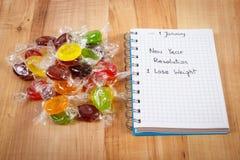 Nouvelles années de résolutions écrites en carnet et sucreries Photo stock