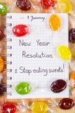 Nouvelles années de résolutions écrites en carnet et sucreries colorées Photographie stock libre de droits