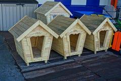 Nouvelles cabines de chien faites de bois sur la rue près du mur Photographie stock