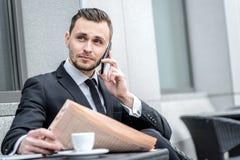 Nouvelles de matin Jeune homme d'affaires sérieux parlant au téléphone et Photos libres de droits