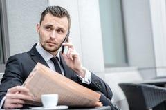 Nouvelles de matin Jeune homme d'affaires sérieux parlant au téléphone et Photographie stock libre de droits