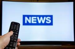 Nouvelles de observation d'homme sur la TV et employer le contrôleur à distance image stock