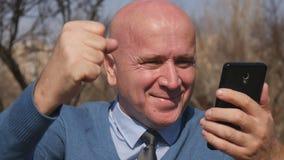 Nouvelles de Read Cellphone Financial d'homme d'affaires enthousiaste les bonnes gesticulent heureux banque de vidéos
