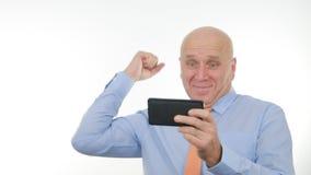 Nouvelles de Reading Unbelievable Good d'homme d'affaires sur la Tablette et faire des gestes heureux photographie stock libre de droits