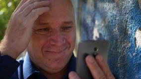 Nouvelles de sourire stupéfaites de lecture heureuse de personne bonnes sur le téléphone portable banque de vidéos