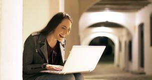 Nouvelles enthousiastes de lecture de femme sur un ordinateur portable pendant la nuit banque de vidéos