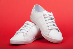 Nouvelles espadrilles blanches sur le fond rouge Photos libres de droits