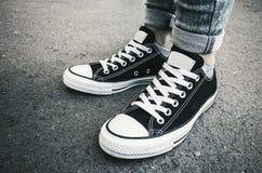 Nouvelles espadrilles noires et blanches, pieds d'adolescent Photos libres de droits