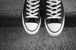 Nouvelles espadrilles noires et blanches, pieds d'adolescent Image stock