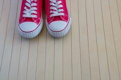 Nouvelles espadrilles rouges sur le fond en bois Photo libre de droits