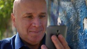 Nouvelles extérieures de Reading Cell Phone d'homme d'affaires regardant et souriant à la caméra banque de vidéos