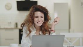 Nouvelles joyeuses de lecture de sourire de femme dans l'ordinateur portable Jeune dame heureuse regardant l'ordinateur banque de vidéos