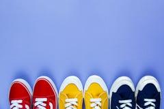 Nouvelles paires d'espadrilles bleues jaunes rouges sur le fond violet avec l'espace de copie Espadrilles de mode de vie photo libre de droits