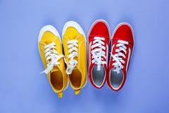 Nouvelles paires d'espadrilles jaunes rouges sur le fond violet avec l'espace de copie Espadrille de mode de vie photographie stock libre de droits