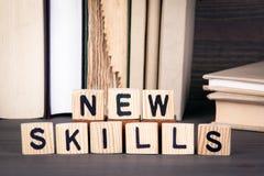 Nouvelles qualifications, lettres en bois sur la table en bois Fond d'éducation, de succès et de communication photographie stock libre de droits