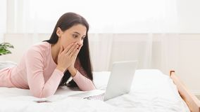 Nouvelles stupéfaites de lecture de femme sur l'ordinateur portable, se trouvant sur le lit à la maison photo stock