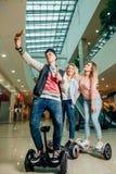 Nouvelles technologies modernes trois personnes sur le hoverboard faisant le selfie photos libres de droits