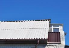 Nouvelles tuiles de toit d'amiante dangereux avec la fenêtre de toit, la lucarne et le petit balcon Photo libre de droits