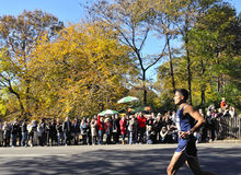 Nov 7: Crowd cheers NYPD runner NYC Marathon 2010. New York, NY Nov 7: NYPD runner cheered by crowd during last few miles of race in Central Park NYC Marathon stock image