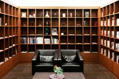 Minimalist lounge with black leather couch in library with wooden bookshelf royalty free stock images