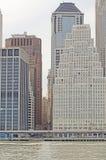 nov.- 27 2018, New York, New York En sikt ner Wall Street från Eastet River som visar Treenighetkyrkan och den högväxta byggnaden royaltyfri bild