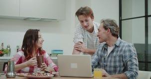 Nova geração de jovens, filho para explicar a seus pais maduros como usar uma nova tecnologia usando um portátil que senta-se em vídeos de arquivo