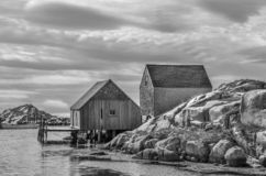 Peggy`s Cove, Nova Scotia fishing sheds with rocky cliffs iin black and white. royalty free stock image