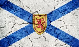 Nova Scotia, province of Canada, flag. On dry earth ground texture background Stock Photography