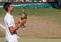 Novac Djokovic, jugador servio, gana Wimbledon por cuarta vez En la foto él sostiene su trofeo en corte del centro foto de archivo libre de regalías