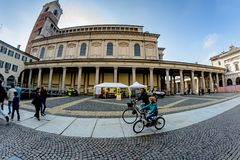 Novara Italien - Oktober 17, 2016: Mamma- och sonritten cyklar på gatan i bakgrunden av en forntida byggnad arkivfoto