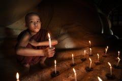 Novato budista con luz de una vela Foto de archivo