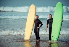 Novato e instrutor do surfista em uma praia com prancha imagem de stock