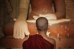Novatos budistas que se encienden encima de luz de una vela Fotografía de archivo
