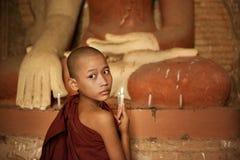 Novatos budistas que se encienden encima de luz de una vela en templo Fotografía de archivo libre de regalías
