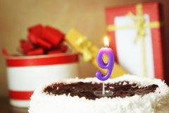 Nove anos de aniversário Bolo com vela e os presentes ardentes Imagens de Stock