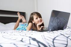 Nove anos de criança idosa que tem o divertimento usando o portátil em seu quarto imagem de stock