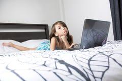 Nove anos de criança idosa que tem o divertimento usando o portátil em seu quarto fotografia de stock royalty free