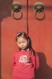 Nove anos de menina chinesa bonito idosa na frente de sua casa, Pequim, China Foto de Stock Royalty Free