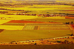 Nove Kopista wioska między złoto polami gdy przeglądać od wzgórza Radobyl w CHKO Ceske Stredohori terenie przy zmierzchem w czesk Obraz Royalty Free