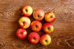 Nove maçãs em uma tabela de madeira Fotos de Stock Royalty Free
