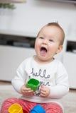 Nove meses de bebê idoso que joga com seus brinquedos Imagens de Stock